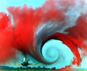 Circular tip vortex generated by a plane's wing visualized using coloured smoke. The smoke on the right hand side is being pulled away from the ground by the upwash while smoke on the left is pushed down towards the ground by the downwash.
